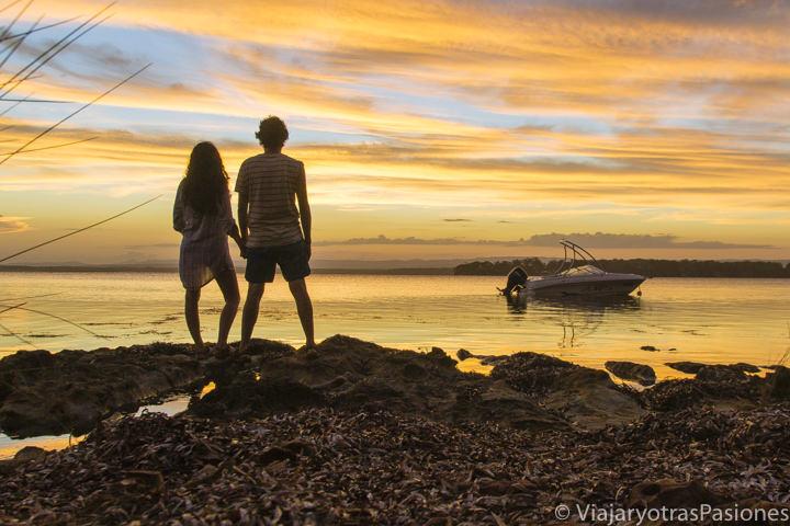 Pareja frente a un increíble atardecer en Jervis Bay, Australia
