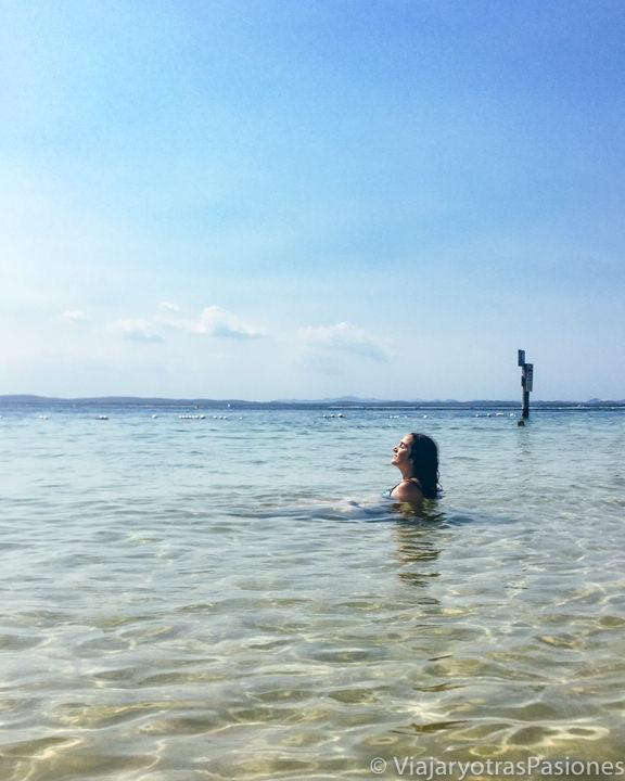 Haciendo el baño en la agua transparente de Little Beach en Port Stephens, Australia