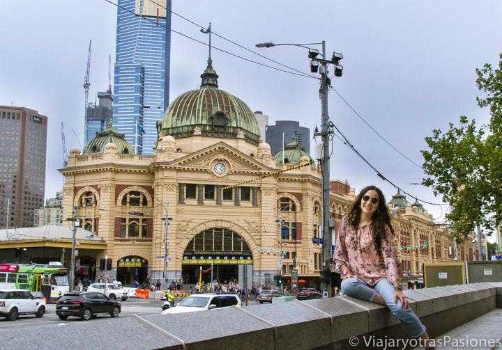 Sonriente de frente a la famosa estación de los trenes de Flinders Street, en Melbourne en Australia