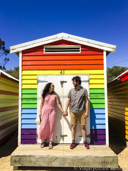 Pareja sonriente en una de las casetas de colores en Brighton Beach en el viaje a Melbourne y Victoria en Australia