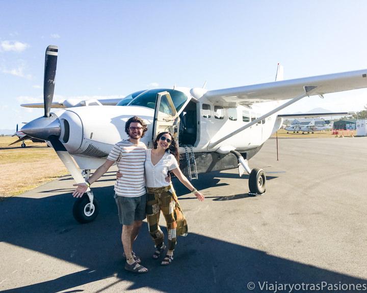 Pareja frente al avión que sobrevuela la Gran Barrera de Coral, Australia