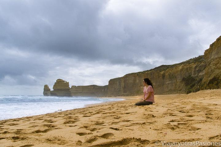 Sentada en la increíble playa cerca de los Doce Apóstoles en recorrer la Great Ocean Road en Australia