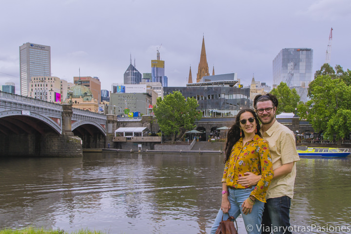 Pareja sonriente cerca del río Yarra frente al bonito CBD de Melbourne en Australia